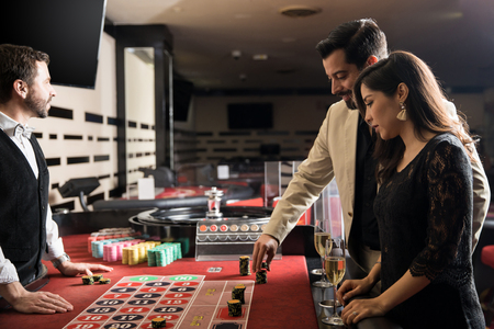 Good looking young couple doing on a date at a casino and having some fun playing the roulette