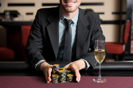 Closeup of a confident man with a winning hand going all in during a poker game in a casino