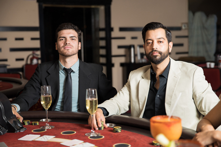 Portrait of two male card players betting some and playing cards in a casino