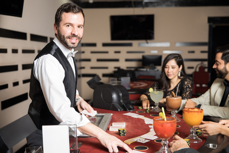 Portrait of a handsome Hispanic card dealer playing blackjack in a casino Stock Photo
