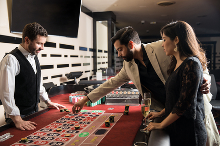 Profile view of a young Hispanic couple looking serious and placing a bet in a roulette wheel at a casino