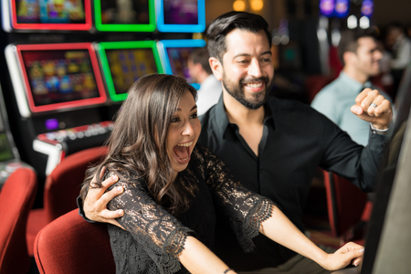 Good looking young couple celebrating and looking excited about hitting the jackpot in a slot machine at a casino