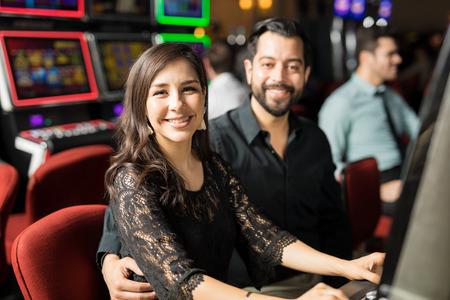 Portrait d'un heureux jeune couple hispanique datant et s'amuser à jouer aux machines à sous dans un casino Banque d'images - 92613341