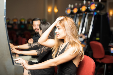 Caucasian young woman sitting in a slot machine at a casino and looking worried after losing some money