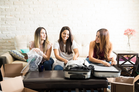 Cute young woman unpacking her things and getting help from her friends while moving in