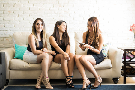 Attractive young woman and her friends making plans for the night while getting ready at home Banque d'images
