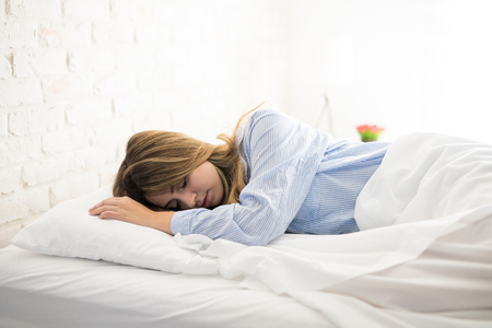 Beautiful young woman in pajamas sleeping on her bed while the sun rises in the morning
