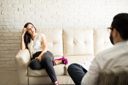 Pretty young hispanic female patient sitting on couch and sharing problems with male psychotherapist  Archivio Fotografico