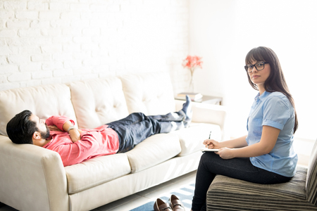 Beautiful female psychologist sitting in the chair with her patient lying on sofa
