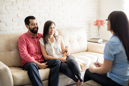 Loving hispanic couple sitting on couch during psychotherapy session.