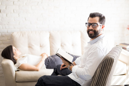 Professional male psychologist holding a diary with female patient lying on sofa at the back Stock Photo