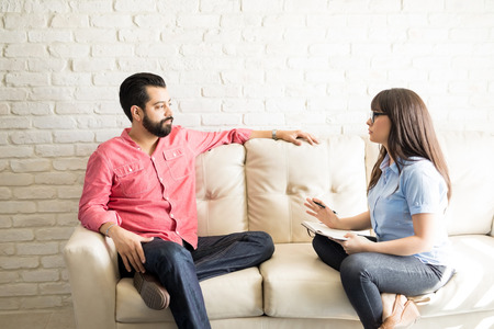 Female psychiatrist explaining diagnosis and treatment to male patient during therapy in her office Stock Photo