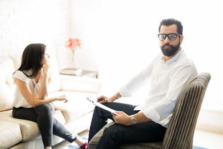 Professional experienced therapist sitting on chair with depressed female patient at the back looking away