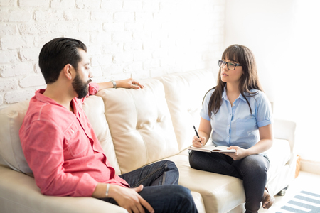 Beautiful young hispanic female psychologist talking with depressed man while sitting on sofa in the office