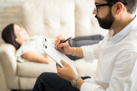 Psychologist making notes during a psychotherapy session with female patient   Stock Photo