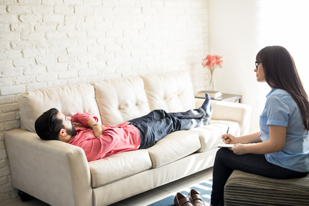 Man lying of sofa and sharing his problems with psychiatrist making notes