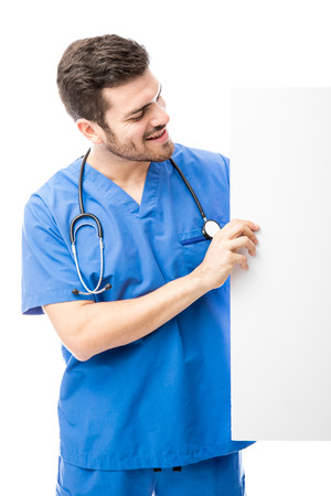 Good looking health professional in scrubs holding a white sign on the side and looking at it
