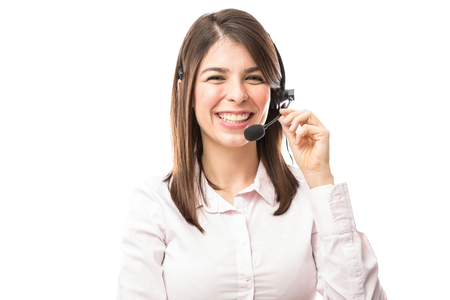 Good looking young woman wearing a headset and working in a call center with a smile Stock fotó