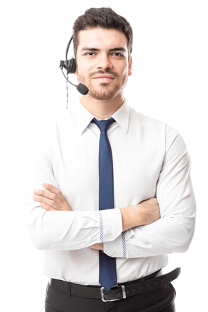 Portrait of a confident young man working at a call center with his arms crossed