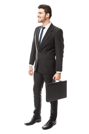 Attractive young Latin businessman with a briefcase looking ready for work in a studio