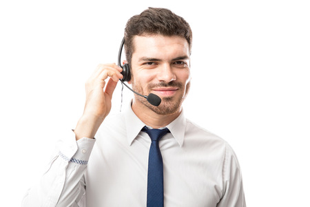 Customer support tech wearing a headset and talking to a customer against a white background Stock Photo