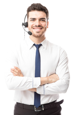 Attractive young Hispanic sutomer support tech working in a call center with a smile