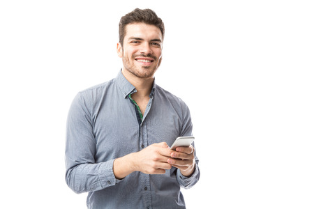 Portrait of a good looking guy looking happy while checking social media on a smartphone