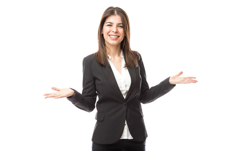 Cute young female hostess wearing a suit and opening her arms while welcoming people Stock Photo