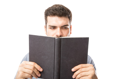 Hispanic smart young man looking busy reading a book in a studio