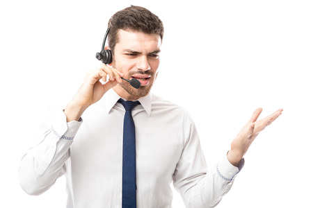 Attractive male call center representative looking angry and talking rudely to a customer over the phone