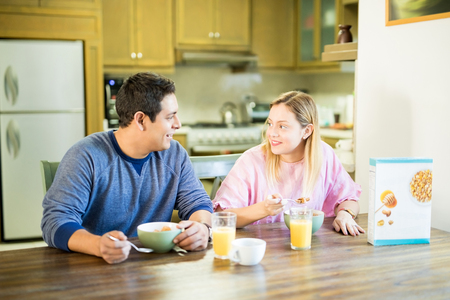 Young hispanic couple enjoying breakfast together in their kitchen and looking at each other Stock Photo