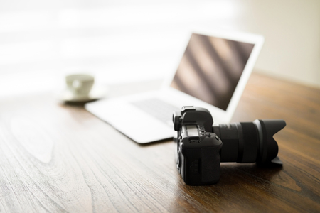 Professional DSLR camera on wooden table with open laptop and cup of coffee in background Zdjęcie Seryjne