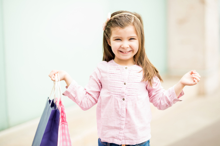 Portrait of a cute young girl carrying shopping bags and smiling while standing outside a mall Stock Photo