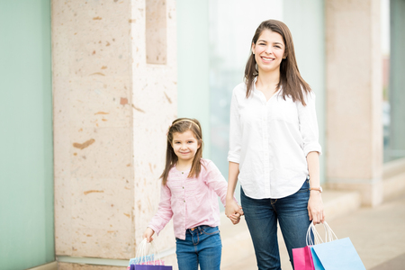 Portrait of cute mother and daughter walking around a mall with shopping bags