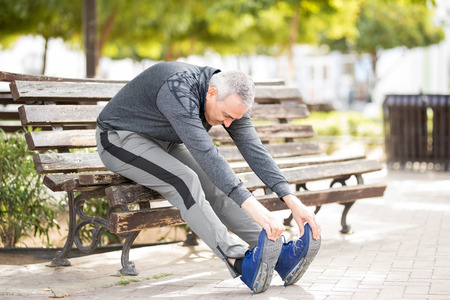 Mature Latin man sitting on a city park bench stretching and touching his toes
