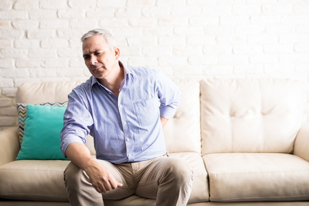 Mature man with gray hair having back pain while sitting on a couch at home