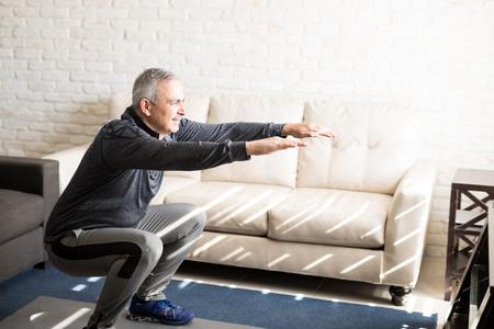 Älterer Mann, der Kniebeugen tut und im Wohnzimmer zu Hause trainiert Standard-Bild