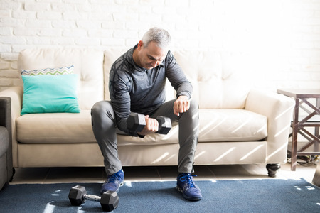 Hispanic man in his 50s sitting on sofa in living room and exercising, lifting dumbbells.