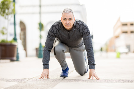 Portrait of mature Hispanic man in the ready position before going for a run in the city Foto de archivo