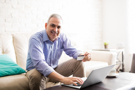 Middle aged man doing some online shopping with his credit card and laptop while sitting at home and smiling