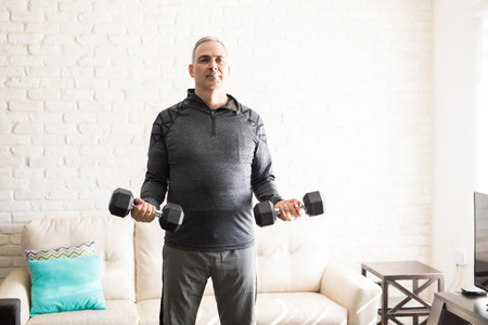 Good looking mature man standing in the middle of the living room and exercising with dumbbells