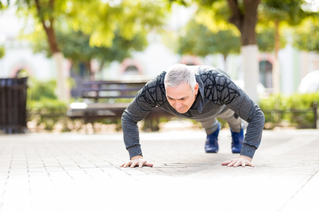 Strong mature man exercising outdoors in a park and doing push ups