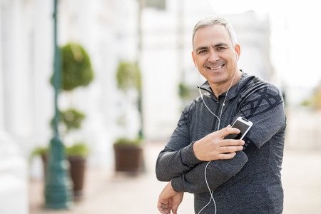 Portrait of handsome hispanic man with mobile phone on his armband looking ready for workout in the city