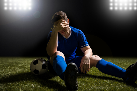 Disappointed soccer player in blue sitting on pitch after losing the match Stock Photo
