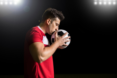 Profile view of young hispanic soccer player celebrate winning at the stadium by kissing a football ball Stock Photo