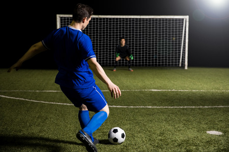 Young soccer player taking a penalty kick against a blurred goalkeeper in the goal Banco de Imagens