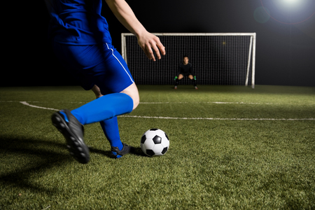 Legs of a soccer player about to kick off the soccer ball from the green grassy sports field towards the goalpost Banco de Imagens