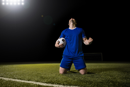 Striker soccer player in blue team celebrating goal in the stadium during match Banque d'images