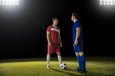 Two professional soccer players standing face to face on football field during match