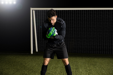 Fit young soccer goalkeeper catching a ball at football goal on field Stockfoto - 97130493